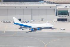 Aeroplano e veicoli di servizio nel terminale di aeroporto immagini stock libere da diritti
