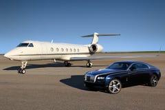 Aeroplano ejecutivo privado de Gulfstream G550 con el coche de lujo de Rolls Royce Wraith mostrado junto en el aeropuerto interna Imágenes de archivo libres de regalías