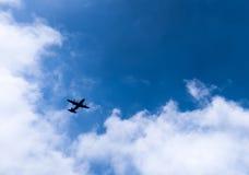 Aeroplano en cielo azul con las nubes Fotografía de archivo
