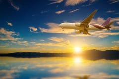 Aeroplano en el cielo en el lago en la puesta del sol Fotografía de archivo libre de regalías