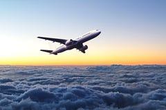 Aeroplano en el cielo en la salida del sol imagen de archivo libre de regalías