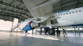 Aeroplano en hangar, vista posterior de aviones y luz de ventanas El jet corporativo privado parqueó en un hangar que hacía frent almacen de video