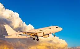 Aeroplano en la mosca en el cielo con puesta del sol de las nubes fotografía de archivo libre de regalías