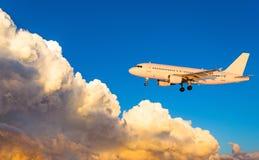 Aeroplano en la mosca en el cielo con puesta del sol de las nubes imagen de archivo