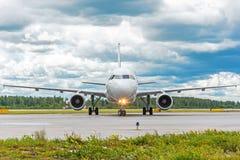 Aeroplano en la pista de la dirección en el aeropuerto, contra el contexto de un cielo pintoresco en las nubes imagen de archivo libre de regalías