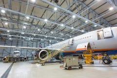 Aeroplano en mantenimiento en el hangar que se prepara para volar Fotografía de archivo libre de regalías