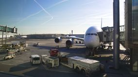 Aeroplano grande que coloca el puente cercano del aire, coche que llega, soporte técnico del aeropuerto almacen de metraje de vídeo
