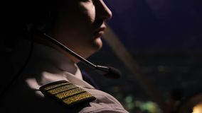 Aeroplano masculino acertado del vuelo del capitán y mirada de la ciudad de la noche, trabajo metrajes