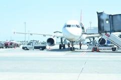 Aeroplano moderno del passeggero parcheggiato al portone del terminal al grembiule di airside dell'aeroporto con il motore a prop immagini stock