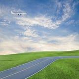 Aeroplano nel cielo con il bello cielo blu e la strada dell'erba verde Fotografie Stock Libere da Diritti