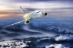 Aeroplano nel cielo sopra le alpi di inverno al tramonto variopinto stupefacente Immagini Stock Libere da Diritti