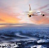 Aeroplano nel cielo sopra le alpi di inverno al tramonto variopinto stupefacente Fotografie Stock