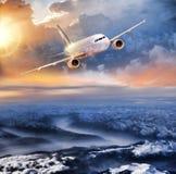Aeroplano nel cielo sopra le alpi di inverno al tramonto variopinto stupefacente Fotografia Stock