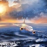 Aeroplano nel cielo sopra le alpi di inverno al tramonto variopinto stupefacente Immagini Stock