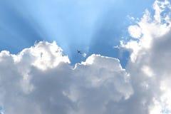 Aeroplano que emerge de las nubes y de las rayas de Sun Fotos de archivo libres de regalías