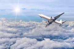 Aeroplano que se va volando adentro a la altitud altísima sobre las nubes blancas Foto de archivo libre de regalías