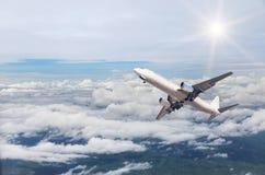 Aeroplano que se va volando adentro a la altitud altísima sobre las nubes blancas Fotos de archivo