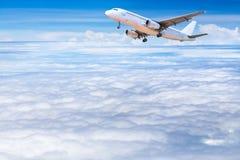 aeroplano que se va volando adentro para despejar el cielo con las nubes blancas Imagen de archivo libre de regalías