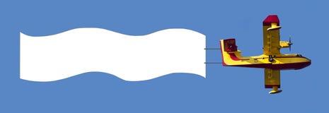 Aeroplano que tira de la bandera blanca del anuncio Fotos de archivo