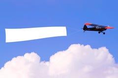 Aeroplano que vuela la bandera en blanco Imagen de archivo libre de regalías