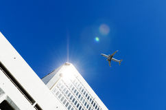 aeroplano que vuela sobre el edificio Foto de archivo libre de regalías