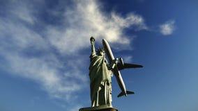 Aeroplano que vuela sobre la estatua de las imágenes de vídeo de la libertad