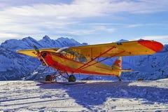 Aeroplano rojo amarillo en el campo de aviación de la montaña en las montañas suizas Imagenes de archivo