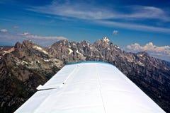 Aeroplano sobre las montañas imagenes de archivo