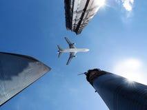 Aeroplano sopra gli edifici per uffici. Immagini Stock