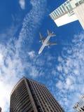 Aeroplano sopra gli edifici per uffici. Immagine Stock