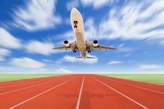 Aeroplano y pista corriente con la hierba verde y el cielo azul c blanca imagen de archivo
