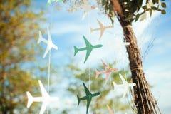 Aeroplanos de papel coloreados en el hilo en fondo del cielo azul el día soleado Imagenes de archivo
