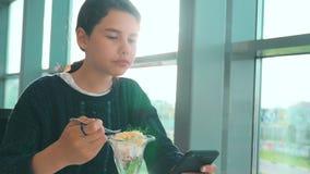 Aeroporto che aspetta un volo in aereo La ragazza teenager di stile di vita mangia l'insalata e guarda lo smartphone Internet in  archivi video