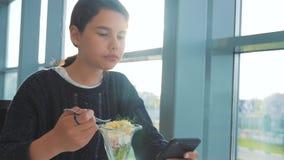 Aeroporto che aspetta un volo in aereo La ragazza teenager mangia l'insalata di stile di vita e lo smartphone di sguardi Internet stock footage
