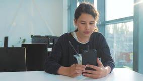 Aeroporto che aspetta un volo in aereo La ragazza teenager mangia l'insalata e guarda lo smartphone di stile di vita Internet in  archivi video