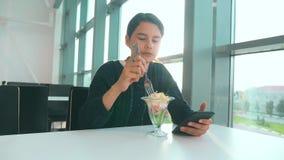 Aeroporto che aspetta un volo in aereo La ragazza teenager mangia l'insalata e guarda lo smartphone Internet in un caff? aeroport archivi video