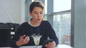 Aeroporto che aspetta un volo in aereo La ragazza teenager mangia l'insalata e guarda lo smartphone Internet in un caff? stile di archivi video
