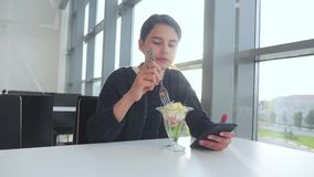 Aeroporto che aspetta un volo in aereo La ragazza teenager mangia l'insalata e guarda lo smartphone Internet in un caff? stile di stock footage