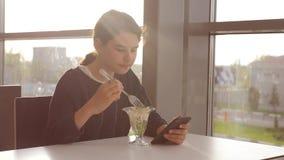 Aeroporto che aspetta un volo in aereo La ragazza teenager mangia l'insalata e guarda lo smartphone Internet in un caff? Aeroport video d archivio