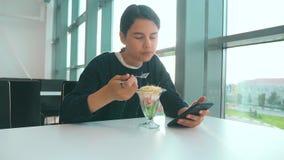 Aeroporto che aspetta un volo in aereo La ragazza teenager mangia l'insalata e guarda lo smartphone Internet in un caff? Terminal video d archivio