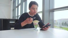 Aeroporto che aspetta un volo in aereo La ragazza teenager mangia l'insalata e guarda lo smartphone Internet in un caff? Terminal archivi video