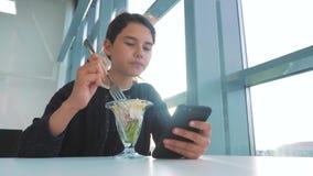 Aeroporto che aspetta un volo in aereo La ragazza teenager mangia l'insalata e guarda lo smartphone Internet in uno stile di vita archivi video