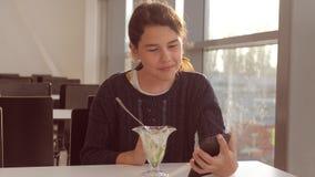 Aeroporto che aspetta un volo in aereo La ragazza teenager mangia l'insalata e guarda lo stile di vita dello smartphone Internet  stock footage