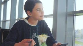 Aeroporto che aspetta un volo di stile di vita in aereo La ragazza teenager mangia l'insalata e guarda lo smartphone Internet in  stock footage