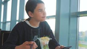 Aeroporto che aspetta uno stile di vita di volo in aereo La ragazza teenager mangia l'insalata e guarda lo smartphone Internet in stock footage