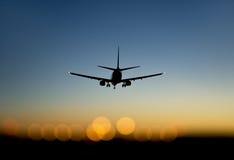 Aeroporto d'avvicinamento degli aerei al tramonto fotografia stock