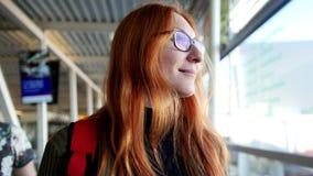 Aeroporto - mulher feliz com cabelo vermelho e os vidros que tomam a escada rolante e que olham à janela vídeos de arquivo