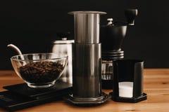 Aeropress, caldera de acero, escalas, amoladora manual, granos de café en la tabla de madera y fondo negro El preparar alternativ imagenes de archivo