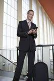 Aeropuerto de Using Cellphone In del hombre de negocios fotografía de archivo