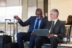 Aeropuerto del ordenador portátil de los hombres de negocios imagenes de archivo